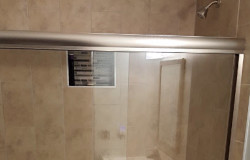 AFTER: Custom tile shower with mosaic accent tile niche and semi-frameless bypass shower door