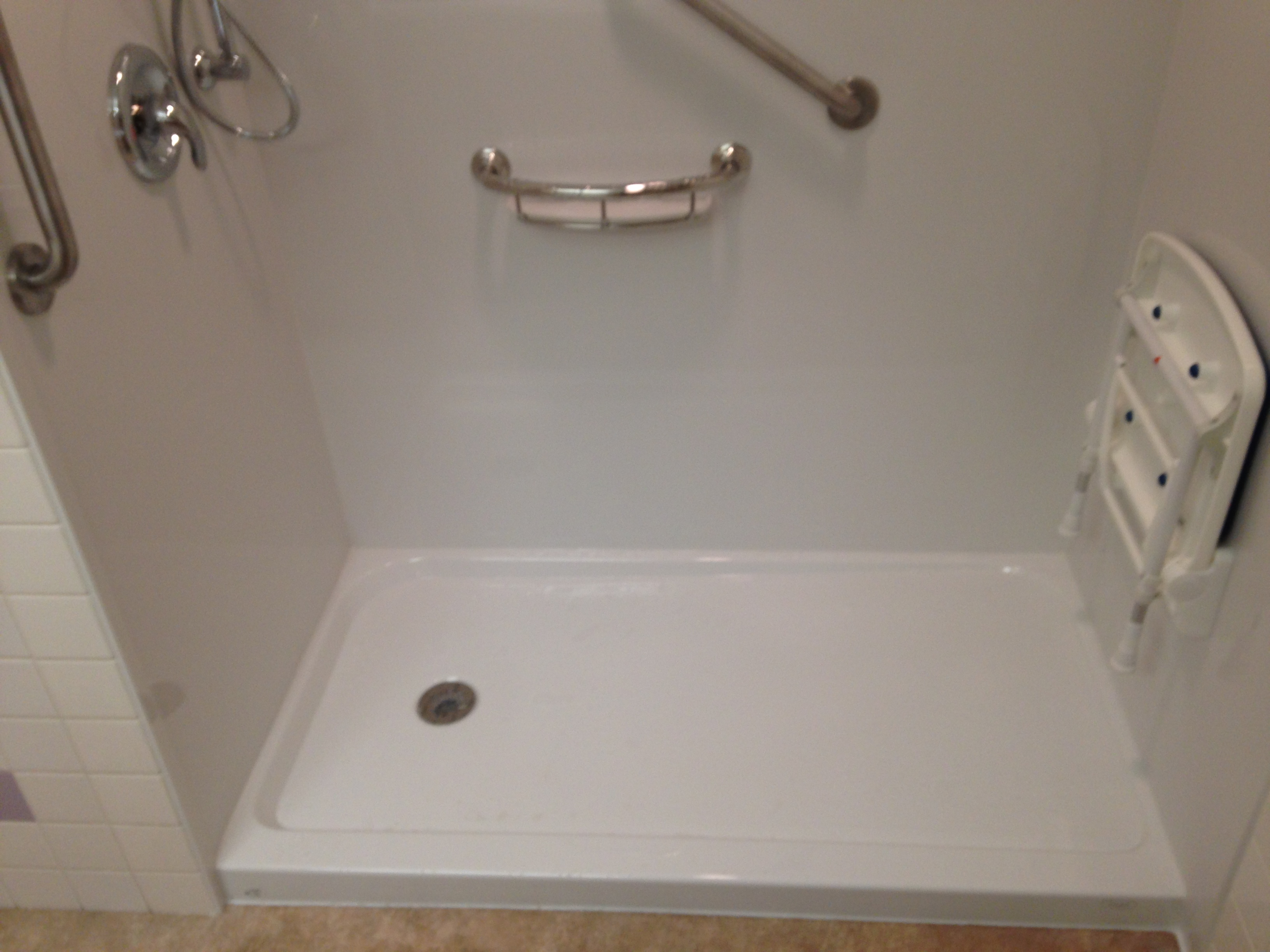after ada accessible shower base with shower seat folded up moen brushed nickel grab bars and chrom fixtures